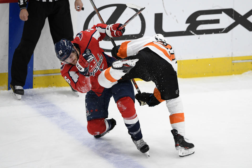 Washington Capitals center Nic Dowd (26) and Philadelphia Flyers center Scott Laughton, right, collide during the first period of an NHL hockey game Saturday, May 8, 2021, in Washington. (AP Photo/Nick Wass)