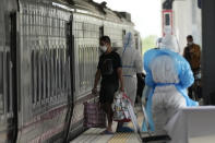 A man, who is among a group of people infected with COVID-19, gets into a train at Rangsit train station in Pathum Thani Province, Thailand to head to his hometown, Tuesday, July 27, 2021. Thai authorities began transporting some people who have tested positive with the coronavirus from Bangkok to their hometowns on Tuesday for isolation and treatment, to alleviate the burden on the capital's overwhelmed medical system. (AP Photo/Sakchai Lalit)