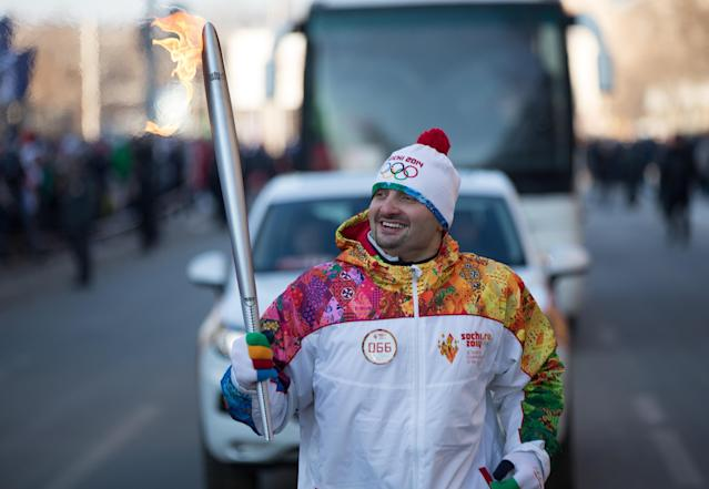 In this photo provided by Olympictorch2014.com torch bearer renown circus artist Edgar Zapashny carries an Olympic torch during the Olympic torch relay in Tyumen, western Siberia, Russia, Wednesday, Dec. 11, 2013. The 65,000-kilometer (40,389 mile) Sochi torch relay, which started on Oct. 7, is the longest in Olympic history. The torch has traveled to the North Pole on a Russian nuclear-powered icebreaker and has even been flown into space. (AP Photo/Olympictorch2014.com)