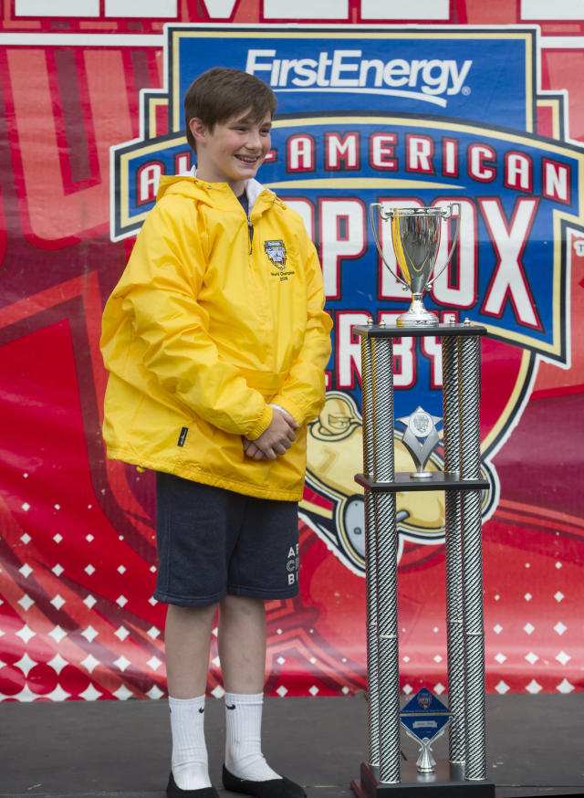 Bradeyn Ditzler of Pottstown, Pa., stands with his trophy after winning the masters division at the First Energy All-American Soap Box Derby, in Akron, Ohio, Saturday, July 21, 2018. (AP Photo/Phil Long)