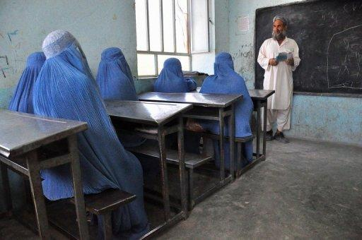 Afghan schoolgirls clad in burqas pay attention to their male teacher in the outskirts of Herat province in 2011. A call by Afghan President Hamid Karzai for more foreign involvement in the country's higher education system risks exacerbating an already dangerous brain drain, analysts warn