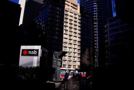 FILE PHOTO: Pedestrians walk past the logo of National Australia Bank which is displayed outside their headquarters building in central Sydney
