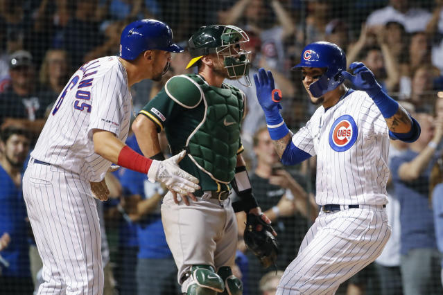 Chicago Cubs' Javier Baez, right, celebrates with Nicholas Castellanos, left, after hitting a two-run home run against the Oakland Athletics during the seventh inning of a baseball game, Monday, Aug. 5, 2019, in Chicago. (AP Photo/Kamil Krzaczynski)
