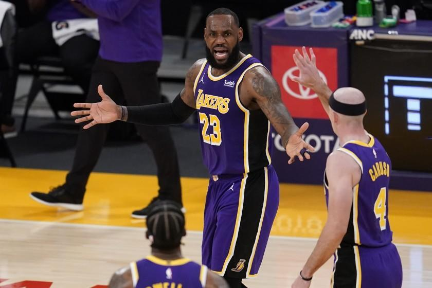 Los Angeles Lakers forward LeBron James (23) talks to teammates during the second half of an NBA basketball game against the Charlotte Hornets Thursday, March 18, 2021, in Los Angeles. (AP Photo/Marcio Jose Sanchez)
