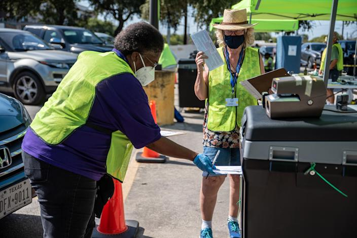 Workers drop voters ballots into a secure box at a ballot drop off location on October 13, 2020 in Austin, Texas. (Sergio Flores/Getty Images)