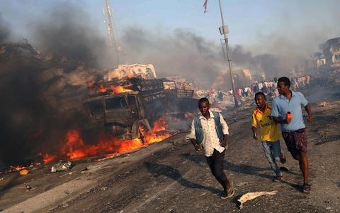 Civilians evacuate from the scene of an explosion in KM4 street in the Hodan district of Mogadishu - Credit: Reuters