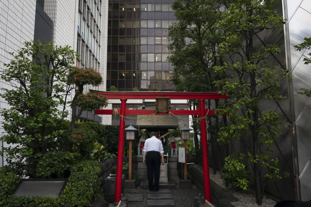 A man prays at a Shinto shrine surrounded by tall buildings in the Chiyoda district of Tokyo, June 3, 2019. (AP Photo/Jae C. Hong)