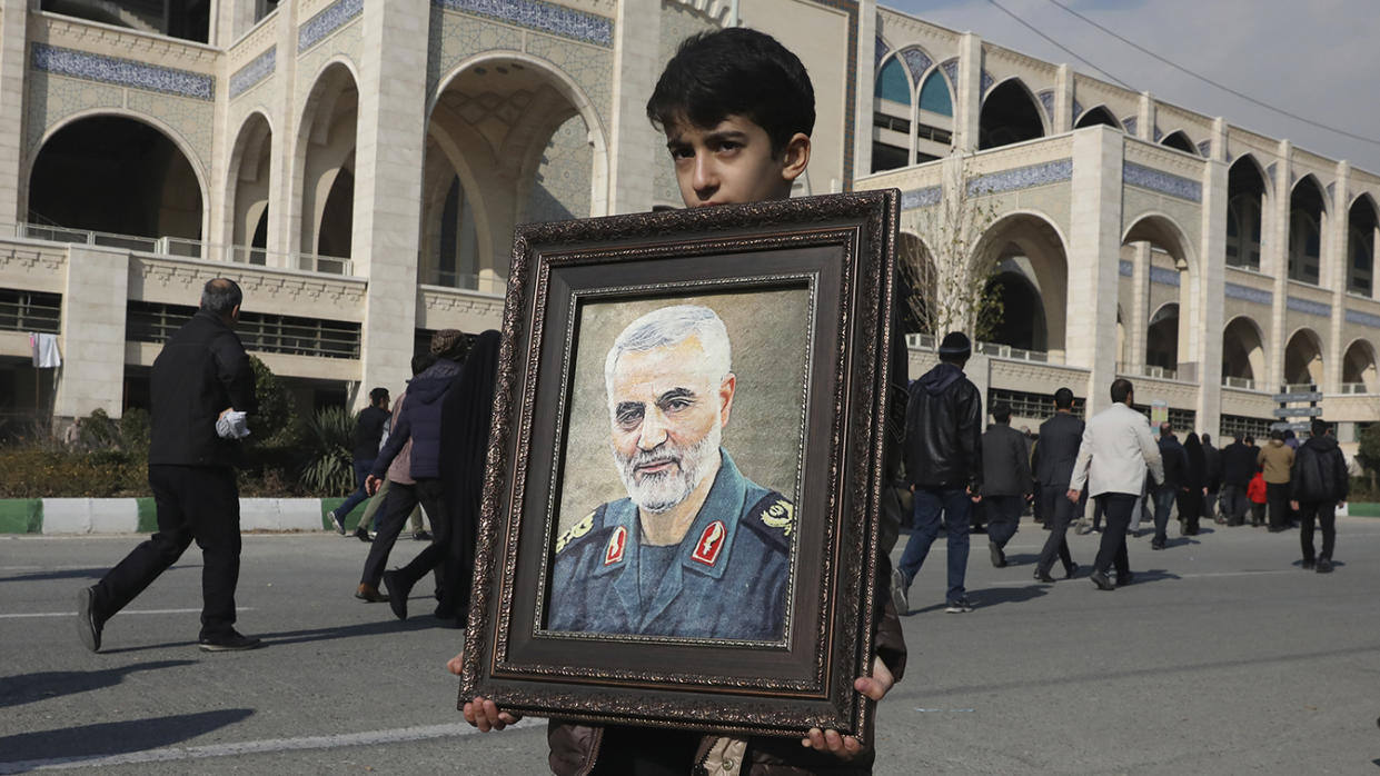 A boy carries a portrait of Iranian Revolutionary Guard Gen. Qassem Soleimani, who was killed in the U.S. airstrike in Iraq, prior to the Friday prayers in Tehran, Iran, Friday Jan. 3, 2020. (Photo: Vahid Salemi/AP)
