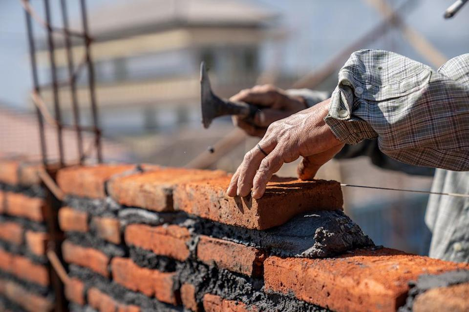 Bricklayer industrial worker installing brick masonry with trowel putty knife at construction site