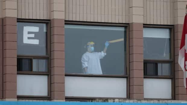A staff member at Ottawa's Carlingview Manor waves from a window on May 15, 2020. An average of 65 per cent of long-term care staff working in Ottawa-area homes have received their COVID-19 vaccine, a CBC data analysis reveals.     (Francis Ferland/CBC - image credit)