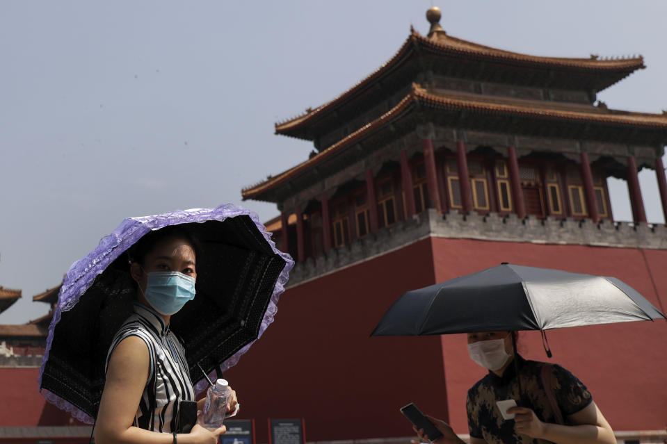 Women wearing face masks to protect against the spread of the new coronavirus look as they visit to Forbidden City in Beijing, Thursday, May 28, 2020. South Korea on Thursday reported its biggest jump in coronavirus cases in more than 50 days, a resurgence that health officials warn is getting harder to track and risks erasing some of the nation's hard-won gains. (AP Photo/Andy Wong)