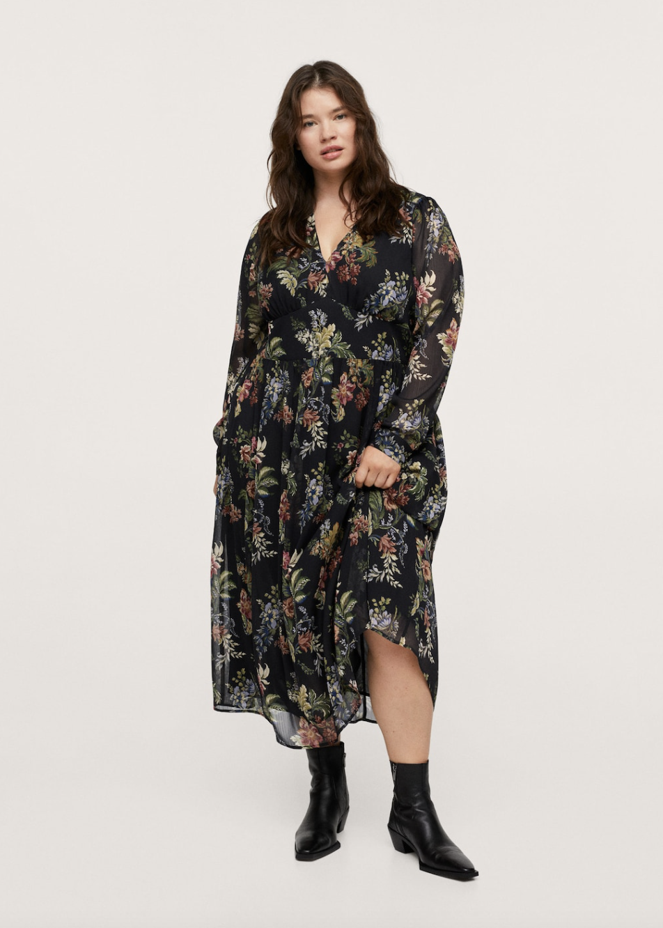 plus size model with brown hair posing in black booties and floral maxi dress