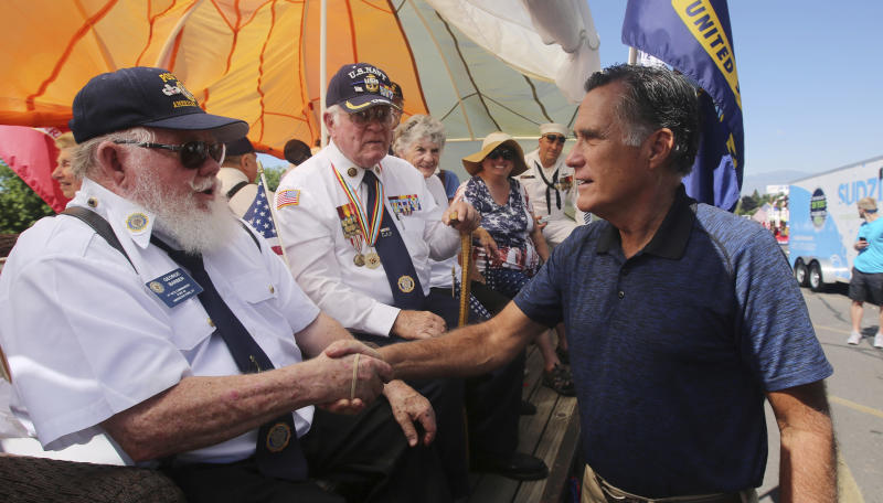 In this Saturday, June 23, 2018, photo, Mitt Romney shakes hands during the Strawberry Day Parade in Pleasant Grove, Utah. Romney faces state lawmaker Mike Kennedy on Tuesday, June 26, 2018, as the ex-presidential nominee looks to restart his political career with the Utah's open U.S. Senate seat. Romney is competing with Kennedy in a primary election to replace U.S. Sen. Orrin Hatch, who is retiring after more than 40 years in office.(AP Photo/Rick Bowmer)