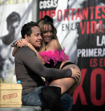 A spectator poses for a picture with a promoter during the inauguration of the 2012 Sex and Entertainment Expo in Mexico City on February 29, 2012. Thousands of visitors are expected to attend the five-day event which will bring together all sorts of sex shows and stands selling toys, videos and magazines from Mexico, the United States and Europe.  AFP PHOTO/Johan ORDONEZ