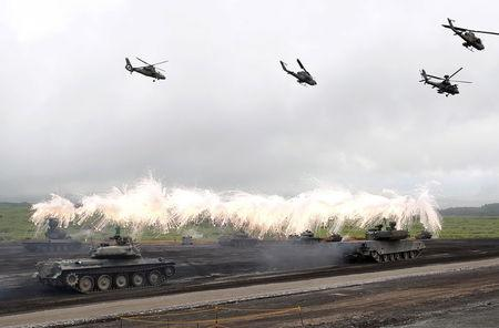 Japanese Ground Self-Defense Force armoured tanks fire during an annual training session near Mount Fuji at Higashifuji training field in Gotemba, west of Tokyo, in this August 19, 2014 file photo. REUTERS/Yuya Shino/Files