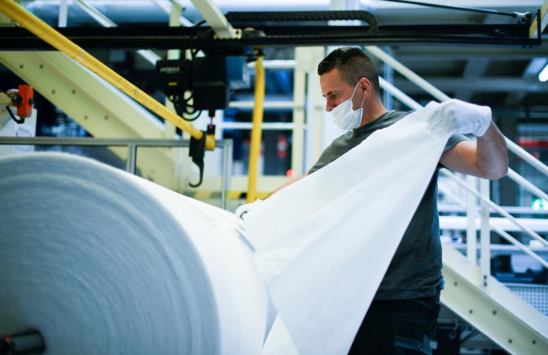 A worker checks the quality of non-woven fabric, produced for protective masks at the Innovatec production facility in Troisdorf, western Germany on June 25, 2020. - The North Rhine-Westphalian company intends to produce an additional 1500 tons of nonwoven matrial per year in the future with the two newly installed subsidized meltblown lines. The additional volume will enable the production of more than 1.5 billion protective masks. (Photo by Ina FASSBENDER / AFP) (Photo by INA FASSBENDER/AFP via Getty Images)