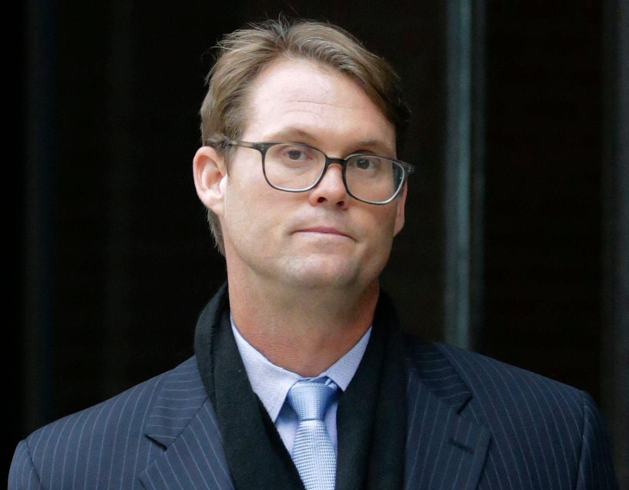 Mark Riddell departs federal court Friday, April 12, 2019, in Boston, after pleading guilty to charges in a nationwide college admissions bribery scandal. (AP Photo/Charles Krupa)