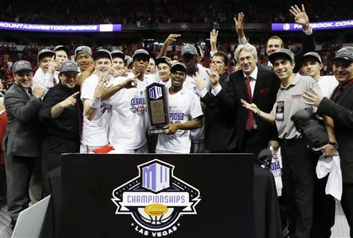 New Mexico players celebrate with the Mountain West Conference tournament championship trophy following an NCAA college basketball game against UNLV on Saturday, March 16, 2013, in Las Vegas. New Mexico defeated UNLV 63-56. (AP Photo/Isaac Brekken)