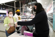 Cashier Druhan Parker, right, works behind a plexiglass shield Thursday, Nov. 19, 2020, as he checks out shoppers Cassie Howard, left, and Paris Black at an in Chicago. The accelerating surge of coronavirus cases across the U.S. is causing an existential crisis for America's retailers and spooking their customers just as the critically important holiday shopping season nears. (AP Photo/Charles Rex Arbogast)