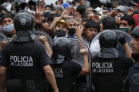 Police block soccer fans waiting to see Diego Maradona lying in state outside the presidential in Buenos Aires, Argentina, Thursday, Nov. 26, 2020. The Argentine soccer great who led his country to the 1986 World Cup title died Wednesday at the age of 60. (AP Photo/Natacha Pisarenko)
