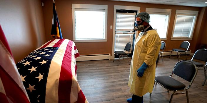 Michael Neel, funeral director of of All Veterans Funeral and Cremation, wearing full PPE, looks at the U.S. flag on the casket of George Trefren, a 90 year old Korean War veteran who died of the coronavirus disease (COVID-19) in a nursing home, in Denver, Colorado, April 23, 2020.