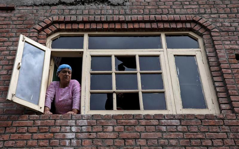 A Kashmiri woman looks out from a window of her house which was allegedly damaged by Indian security after clashes between protesters and the security forces - REUTERS