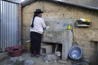 """Maribel Licapa, whose daughter is learning the Quechua Indigenous language at her public primary school, washes clothes at home in Licapa, Peru, Wednesday, Sept. 1, 2021. Licapa said that she was barred from speaking her native language when she worked at a plantation on Peru's coast and as a cleaner in the homes of wealthy families closer to her village. """"You have to speak in Spanish. I don't understand,"""" one employer told her. (AP Photo/Martin Mejia)"""