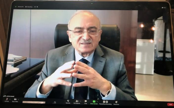 A photograph of a laptop screen shows LAU President Michel Mawad speaking during his online interview with Reuters, in Beirut
