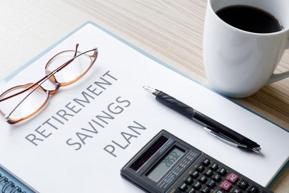 "Binder labeled ""RETIREMENT SAVINGS PLAN"" on a table with a pair of glasses, a calculator, and a pen on top of it and a coffee cup standing next to it."