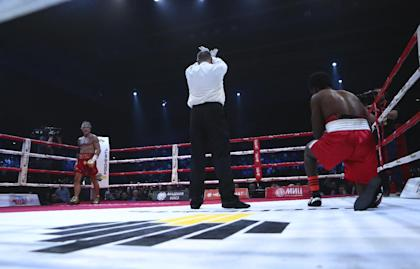 Elliot Seymour (R) struggles to get up as the referee waves off his fight with 62-year-old actor Mickey Rourke (L) in the second round Friday in Moscow. (AP Photo/Denis Tyrin)