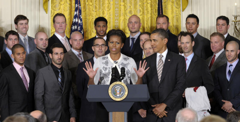 President Barack Obama listens as first lady Michelle Obama speaks in the East Room of the White House in Washington, Tuesday, Jan. 17, 2012, during a ceremony honoring the 2011 World Series baseball Champion St. Louis Cardinals. On Tuesday, Mrs. Obama celebrated her 48th birthday.  (AP Photo/Susan Walsh)