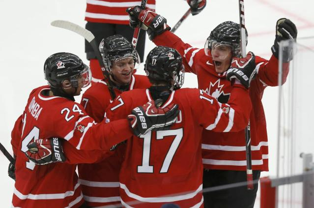 Canada's Mathew Dumba (L), Josh Morrissey (2nd L), Connor McDavid (17) and Bo Horvat celebrate McDavid's goal against the United States during the third period of their IIHF World Junior Championship ice hockey game in Malmo, Sweden, December 31, 2013. REUTERS/Alexander Demianchuk (SWEDEN - Tags: SPORT ICE HOCKEY)