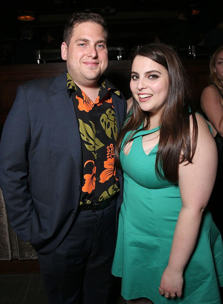 Jonah Hill and Beanie Feldstein are dressed up and pose for a smile at the premiere