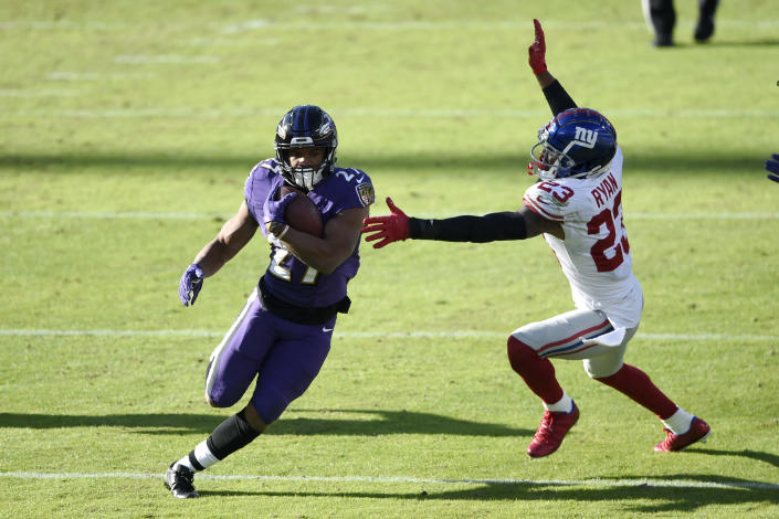 Baltimore Ravens running back J.K. Dobbins (27) runs with the ball as New York Giants free safety Logan Ryan (23) tries to stop him during the first half of an NFL football game, Sunday, Dec. 27, 2020, in Baltimore. (AP Photo/Gail Burton)