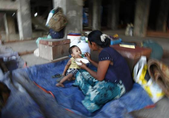 A worker feeds her son at a construction site in Yangon, January 24, 2012.