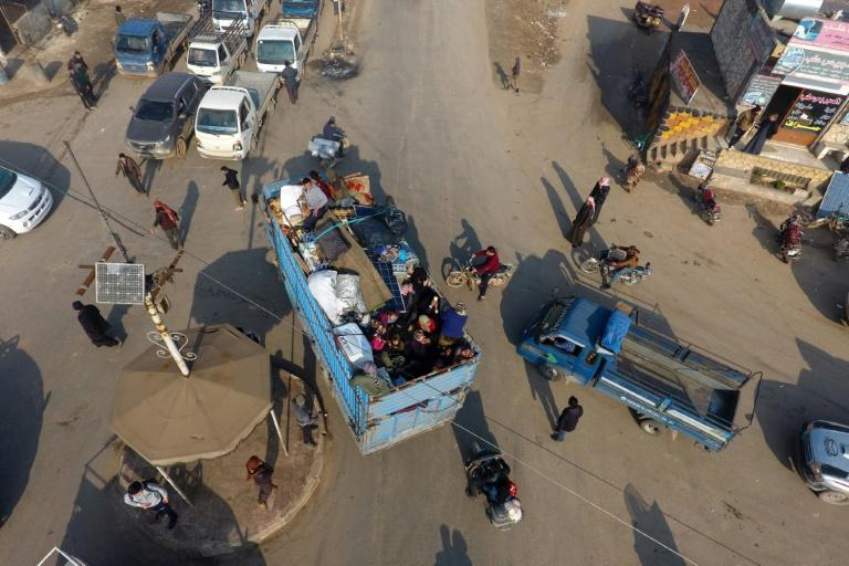 Syrian families flee the village of Hazano, about 20 kilometres northwest of the city of Idlib, towards the Turkish border on Sunday, after the regime stepped up advances against jihadists