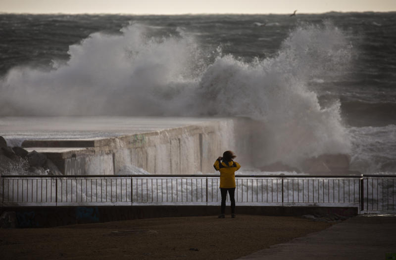 A woman photographs the Mediterranean sea during strong winds in Barcelona, Spain, Monday, Jan. 20, 2020. Two people have died as storms carrying heavy snowfalls and gale-force winds lashed many parts of Spain on Monday. The storm has forced the closure of Alicante airport and some 30 roads in eastern region. Six provinces are on top alert. (AP Photo/Emilio Morenatti)