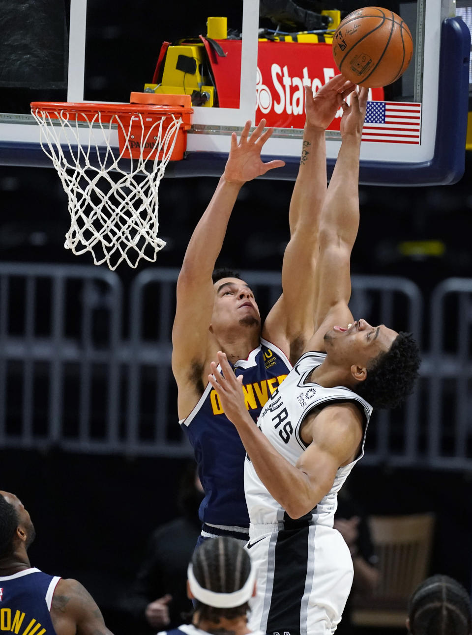 Denver Nuggets forward Michael Porter Jr., left, blocks a last-second shot by San Antonio Spurs forward Keldon Johnson in the second half of an NBA basketball game Friday, April 9, 2021, in Denver. (AP Photo/David Zalubowski)