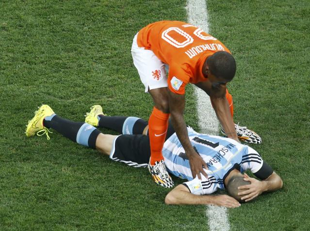 Georginio Wijnaldum of the Netherlands checks on Argentina's Javier Mascherano after colliding during their 2014 World Cup semi-finals at the Corinthians arena in Sao Paulo July 9, 2014. REUTERS/Paulo Whitaker (BRAZIL - Tags: SOCCER SPORT WORLD CUP)