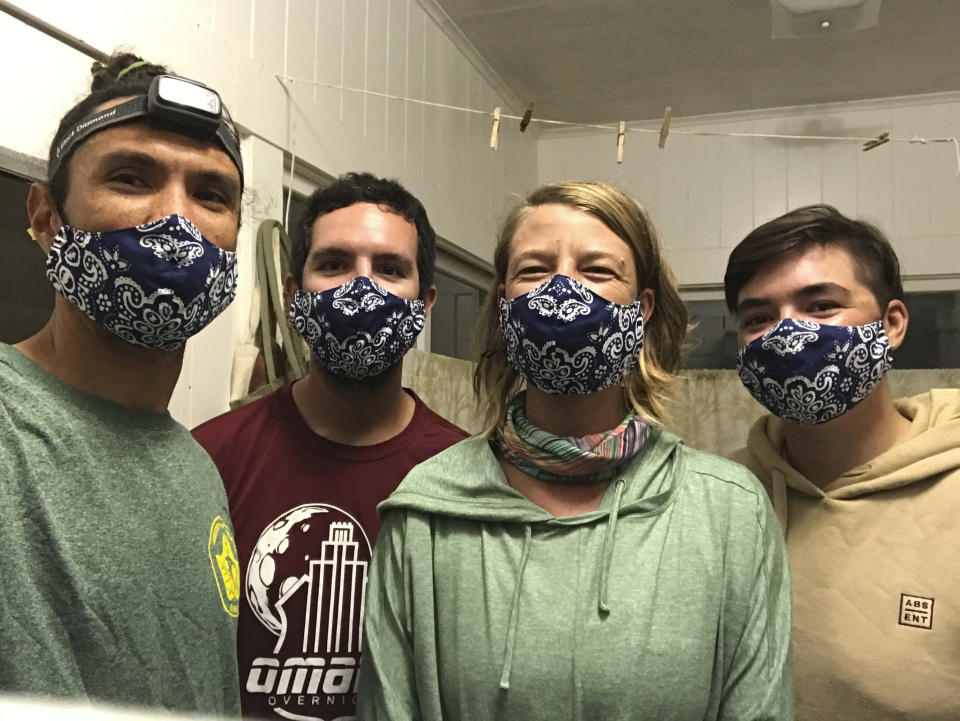 In this Nov. 4, 2020, photo provided by Matt Saunter, Saunter, left, Matt Butschek II, second from left, Naomi Worcester and Charlie Thomas, right, wear masks after arriving in Honolulu from an 8-month expedition to Kure Atoll in the Northwestern Hawaiian Islands. Cut off from the rest of the planet since February, they are back, re-emerging into a society changed by the coronavirus outbreak. (Matt Saunter/Hawaii Department of Land and Natural Resources via AP)