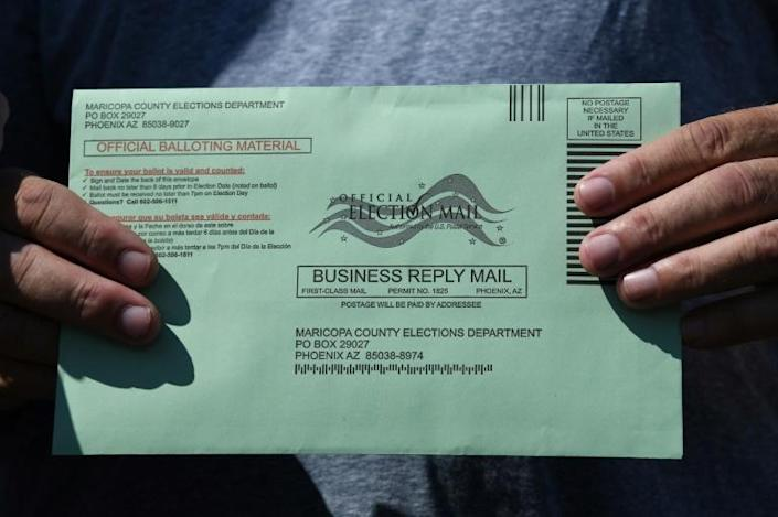 """A voter holds a green envelope containing their ballot in Arizona, where it already """"looks like election day"""""""