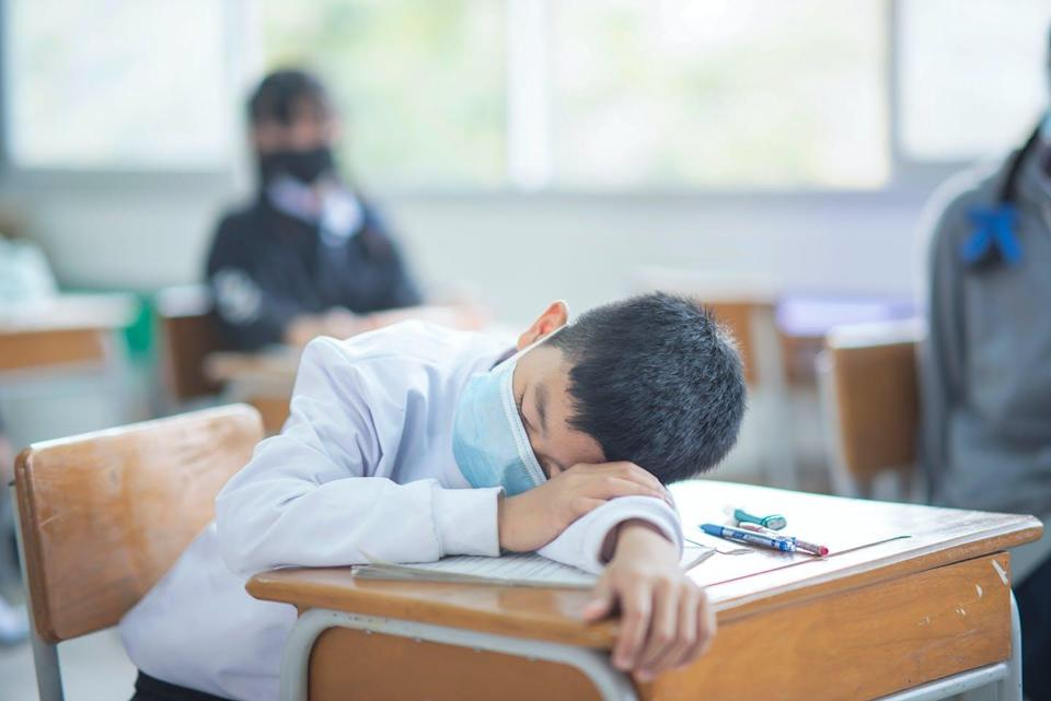 A youth in a face mask has his head laid down on a desk.