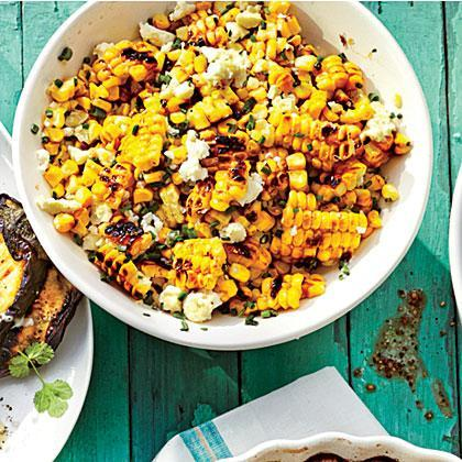 """<p>This quick and easy grilled <a href=""""https://www.myrecipes.com/ingredients/fresh-corn-recipes"""" rel=""""nofollow noopener"""" target=""""_blank"""" data-ylk=""""slk:corn"""" class=""""link rapid-noclick-resp"""">corn</a> salad is a play on esquites, a wildly popular Mexican street food. Also known as corn in a cup, esquites are the cobless equivalent to elotes, grilled Mexican street corn topped with mayonnaise, various spices, and crumbled cojita cheese. Sprinkle on some chipotle powder for an added kick. </p>"""