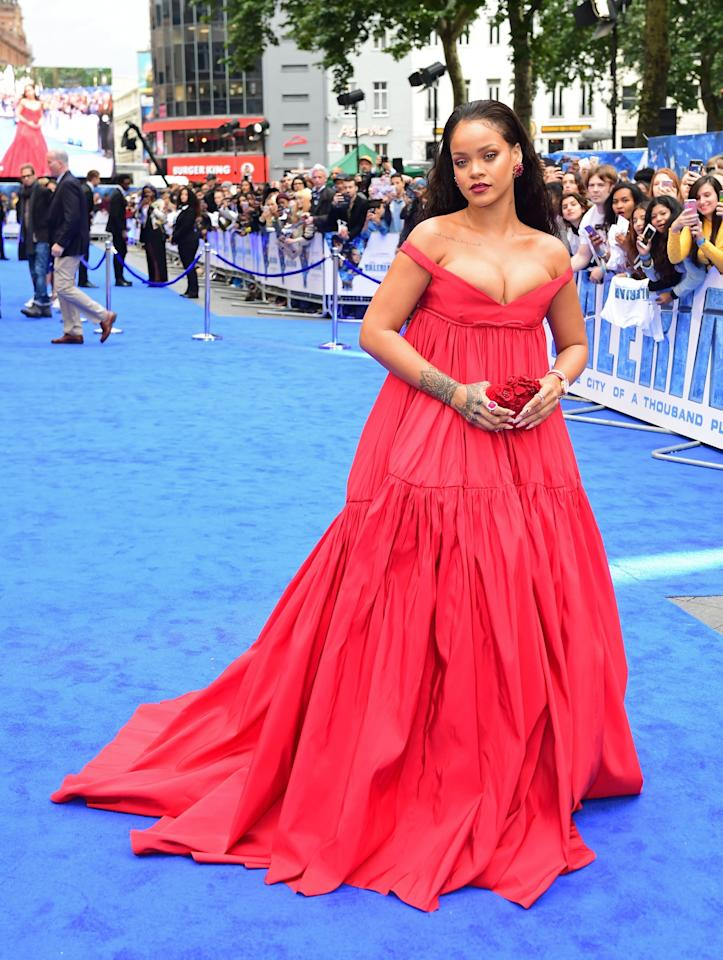 <p>Rihanna went for a couture design by Giambattista Valli once again, hitting the blue carpet in an off-the-shoulder red gown and carrying a rose-hued Jimmy Choo clutch.<br /><i>[Photo: PA]</i> </p>
