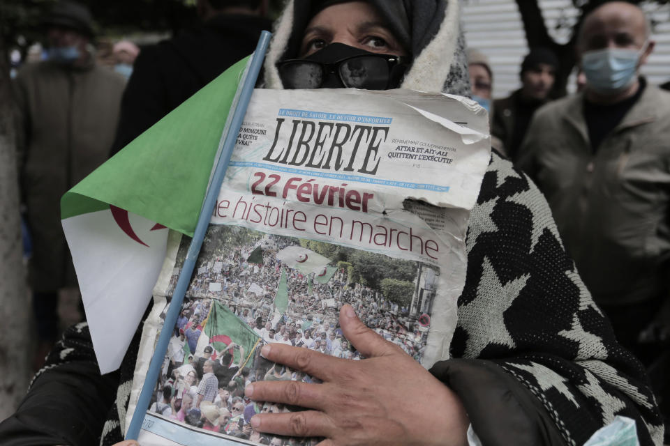 "A woman holds a newspaper headlining ""Feb.22, History coming"" as Algerians demonstrate in Algiers to mark the second anniversary of the Hirak movement, Monday Feb. 22, 2021. Thousands of protesters marking the second anniversary of Algeria's pro-democracy movement took to the streets Monday in the Algerian capital where a wall of security forces stepped aside to let marchers pass. (AP Photo/Toufik Doudou)"