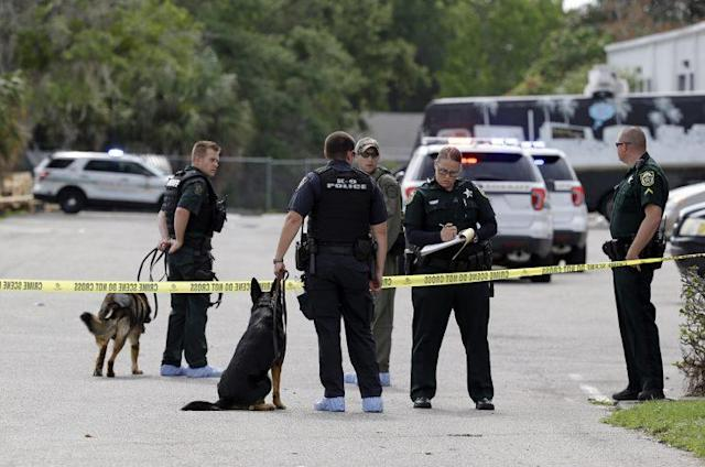 Law enforcement officers, including a K-9 unit, investigate near the scene of a shooting where there were multiple fatalities in an industrial area near Orlando Monday morning. (Photo: John Raoux/AP)