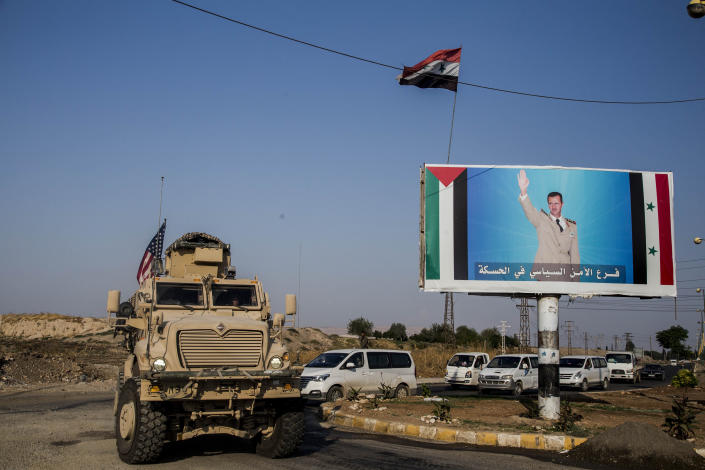 File - In this Saturday, Oct. 26. 2019 file photo, U.S. military convoy drives the he town of Qamishli, north Syria, by a poster showing Syrian President Bashar Aassad. Syrians are marking 10 years since peaceful protests against President Bashar Assad's government erupted in March 2011, touching off a popular uprising that quickly turned into a full-blown civil war. (AP Photo/Baderkhan Ahmad, File)