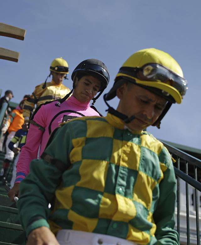 Jockeys walk into the paddock before a race before the 140th running of the Kentucky Derby horse race at Churchill Downs Saturday, May 3, 2014, in Louisville, Ky. (AP Photo/David Goldman)