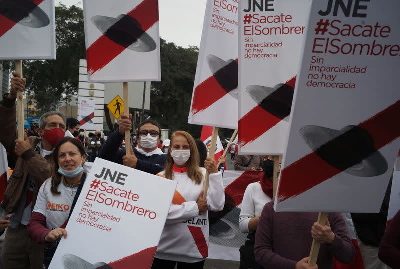 Supporters of Peru's presidential candidate holds signs during a demonstration in Lima