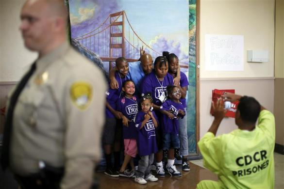 Donte, 34, (back 3rd L), who said he has one year left in prison, and his wife Candy, 31, (4th R) take a family photo in front of a backdrop of the Golden Gate Bridge with their children Mario, 11, Cieara, 7, Nicole, 3, Jada, 4, and Emonnye, 13, (2nd L-2nd R) at San Quentin state prison in San Quentin, California June 8, 2012.